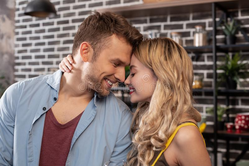 Bearded cheerful husband smiling spending time with lovely woman royalty free stock photo