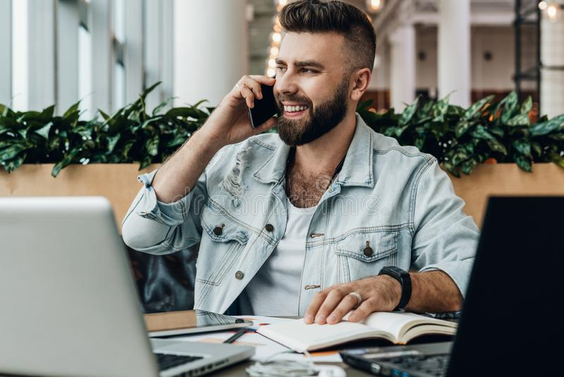Bearded cheerful man is sitting at table in front of laptops, talking on phone. Freelancer has telephone conversations. royalty free stock image