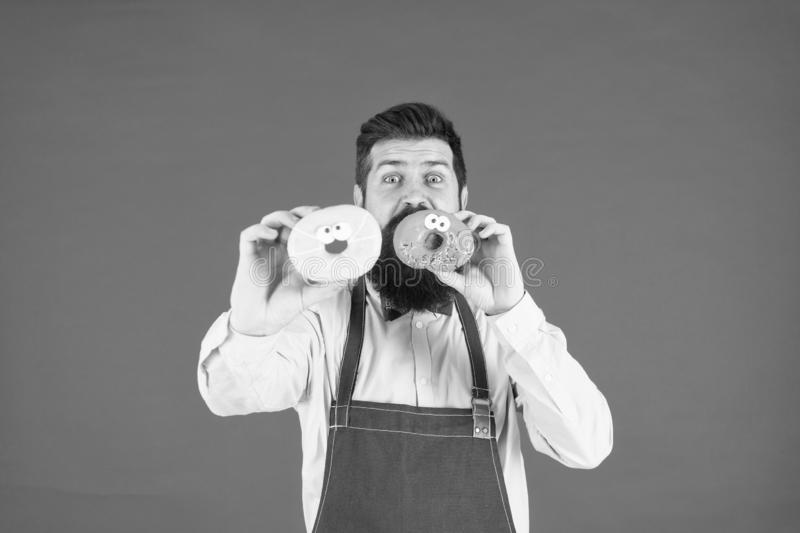 Bearded cheerful well groomed man in apron selling donuts. Bakery owner. Bakery business. Baked goods. Sweets and cakes. Junk food. Hipster bearded baker hold stock image