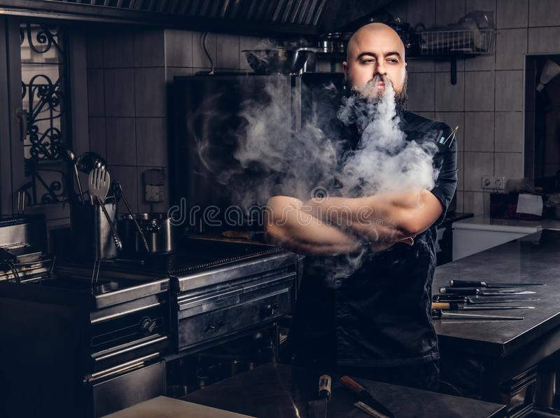 Bearded chef in black uniform smoking e-cigarette while standing in the kitchen. royalty free stock image