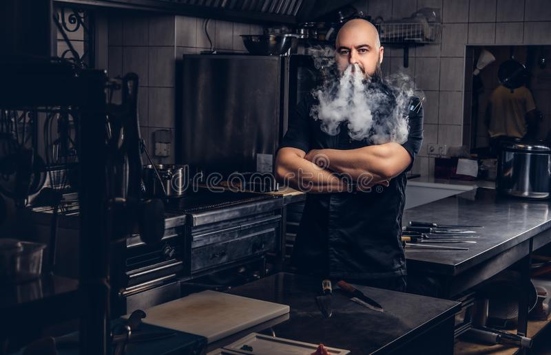 Bearded chef in black uniform smoking e-cigarette while standing in the kitchen. stock photography