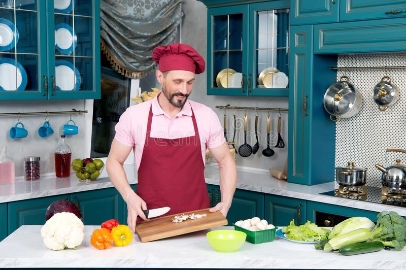 Bearded Chef in cap holds cutting wooden board in hands stock photos