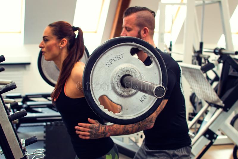 Bearded coach helps a woman in a gym. royalty free stock photography