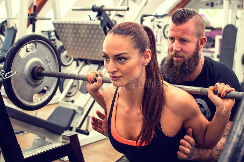 Bearded coach helps a woman in a gym. stock images