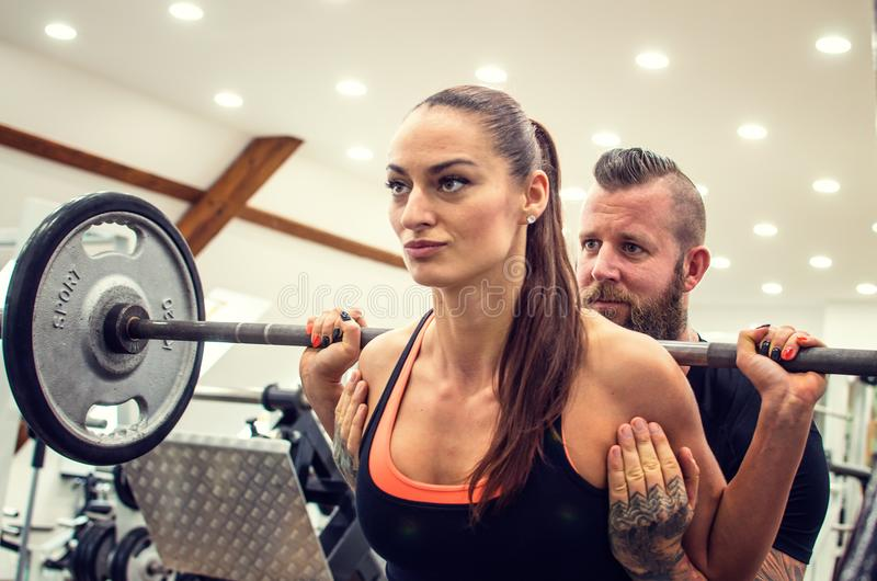 Bearded coach helps a woman in a gym. royalty free stock photo