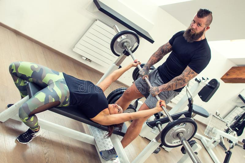 Bearded coach helps a woman in a gym. stock photos