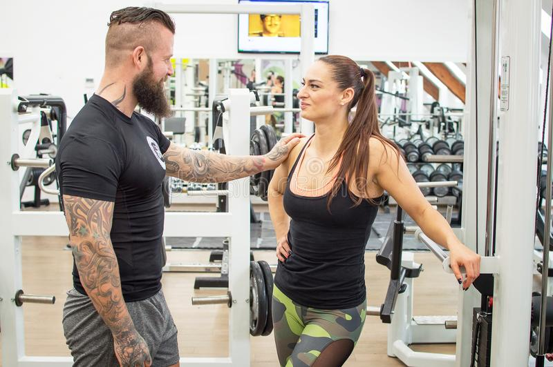 Bearded coach helps a woman in a gym. stock image