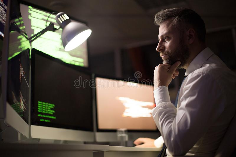 Bearded Coder Concentrated on Work. Profile view of pensive bearded coder wrapped up in work while sitting in front of modern computer, interior of dim office on stock photo