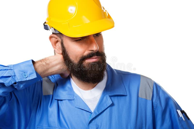 Bearded constructor or builder or foreman in the yellow helmet suffering neck pain. Health insurance concept. Isolated over white stock photo