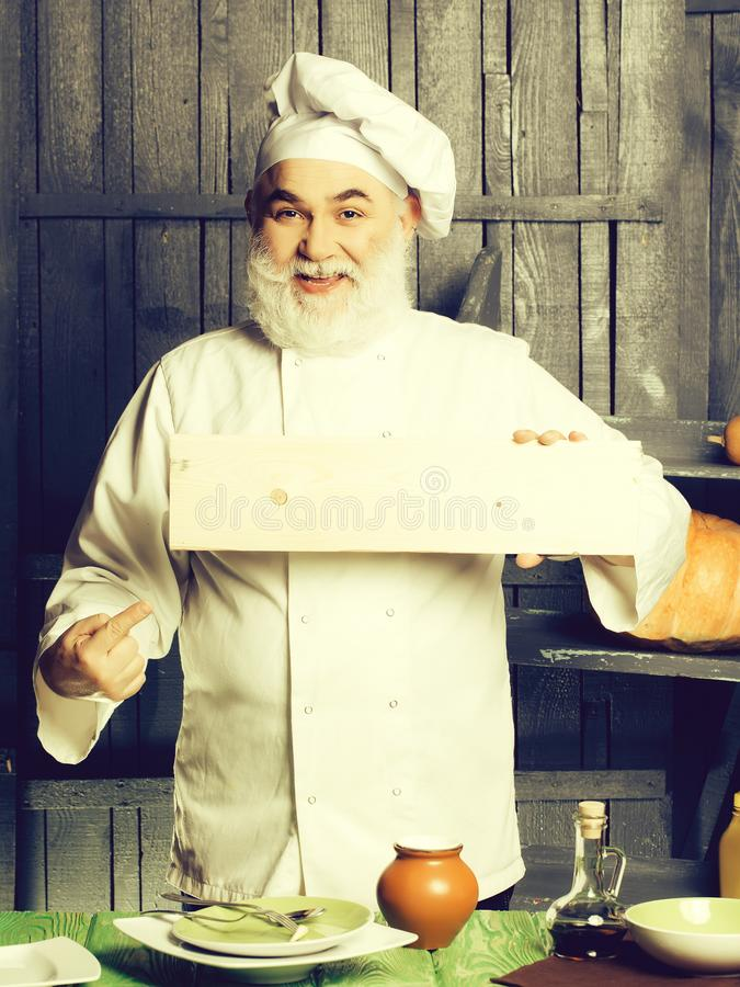 Bearded cook with wooden plate stock photo