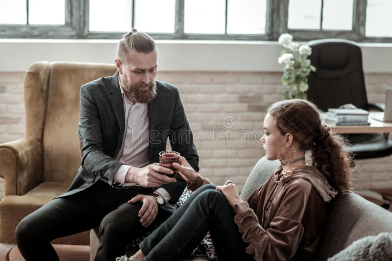 Bearded counselor bringing glass of water to nervous teenager. Bringing water. Bearded professional pleasant counselor bringing glass of water to nervous stock photos
