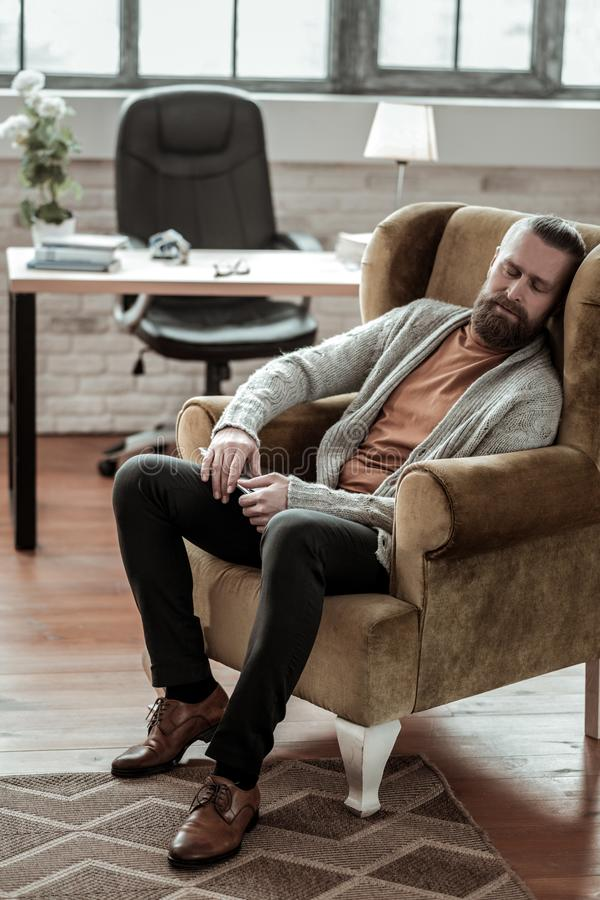Bearded counselor wearing grey cardigan falling asleep. Falling asleep. Bearded counselor wearing grey cardigan falling asleep in his armchair at work royalty free stock images