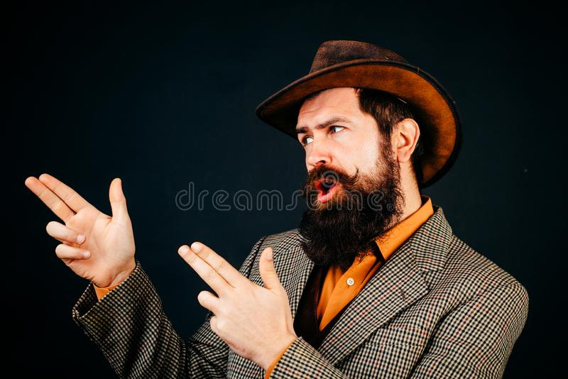Bearded cowboy in suit and hat  at black background. Hipster self confident man wearing retro style suit and hat royalty free stock photography