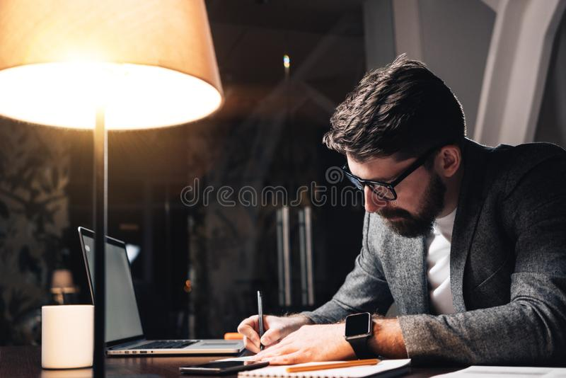 Bearded coworker working by the wood table with laptop. Creative business man make new startup at night loft office. Using modern stock photos
