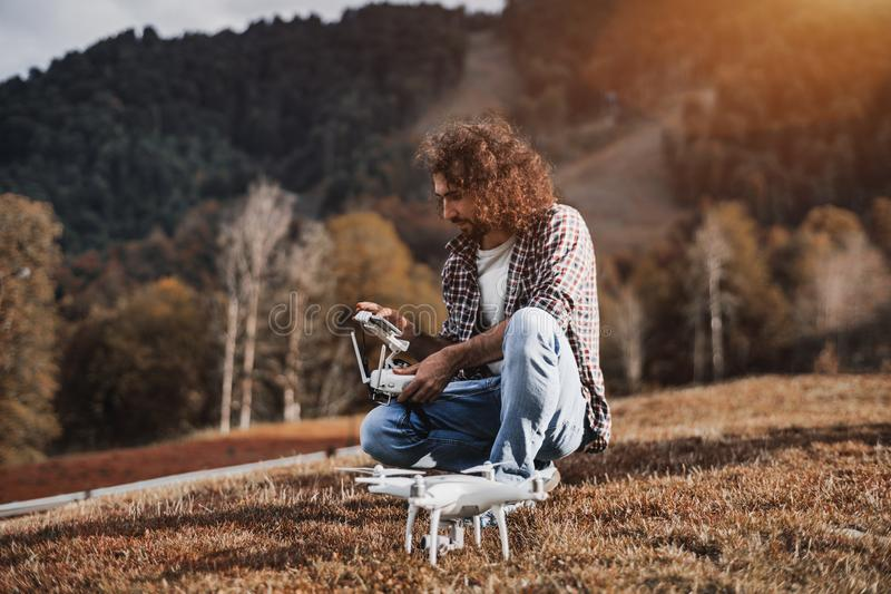 The curly man with beard preparing to launch the quadcopter royalty free stock images
