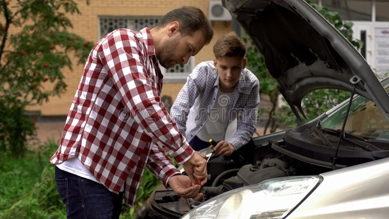 Bearded dad and his son repairing car with open hood outdoors, fixing engine stock photography