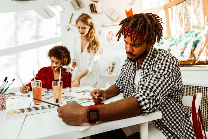 Bearded dark-haired art student with dreadlocks drawing. Man drawing. Bearded dark-haired art student with dreadlocks wearing red smart watch drawing stock photography