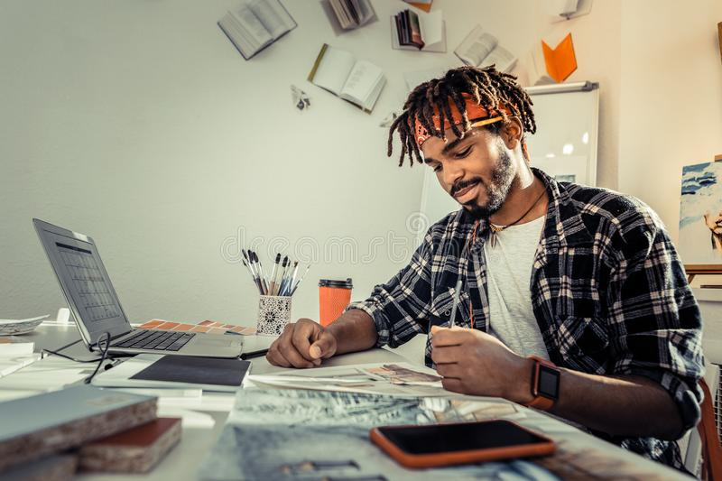 Bearded dark-haired artist with dreadlocks holding pencil. Holding pencil. Bearded dark-haired artist with dreadlocks holding pencil while drawing sketches stock image