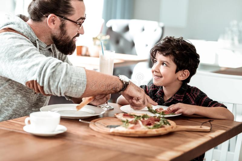 Bearded dark-haired father wearing glasses tasting cheesy pizza stock images