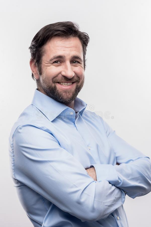 Bearded dark-haired office manager standing on front of white wall royalty free stock photography