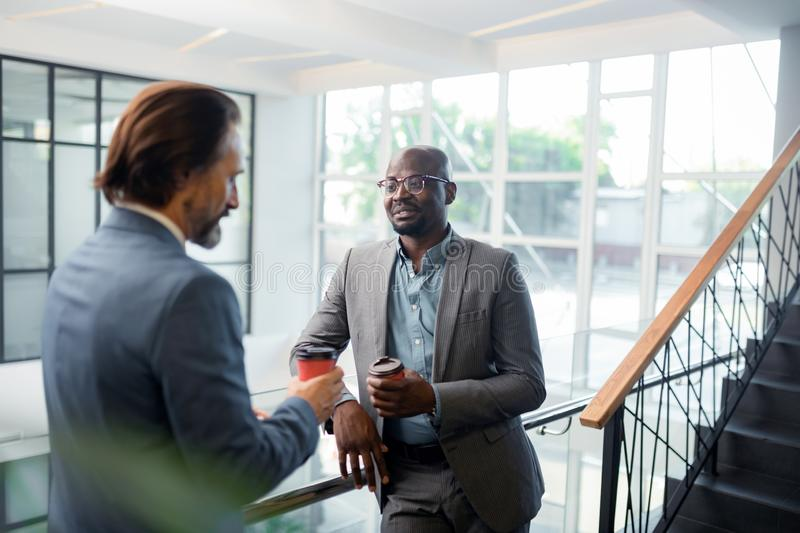 Bearded dark-skinned man wearing glasses speaking with colleague stock photo