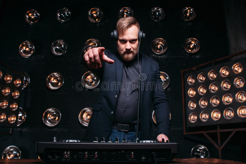 Bearded DJ at mixer plays music on club party stock photography