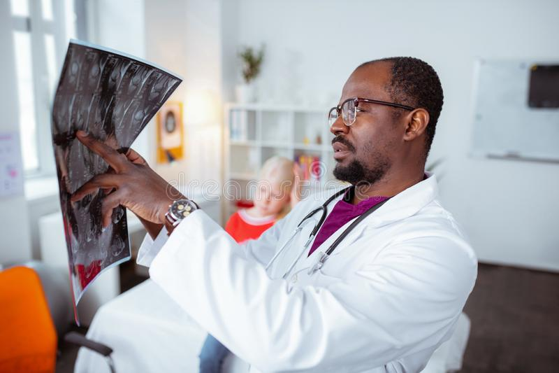Bearded doctor looking at x-ray of little blonde girl stock photography