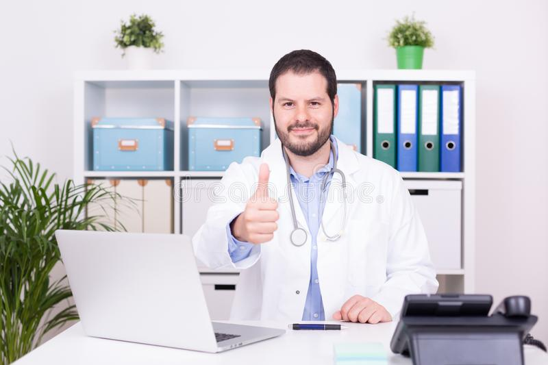 Bearded doctor working at his office showing thumbs up. Business and medical concept stock photo