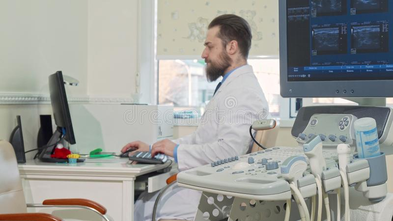 Bearded doctor working at his office, ultrasound scanner on the foreground. Selective focus on ultrasound sonogram scanning machine at the clinic, doctor on stock photography