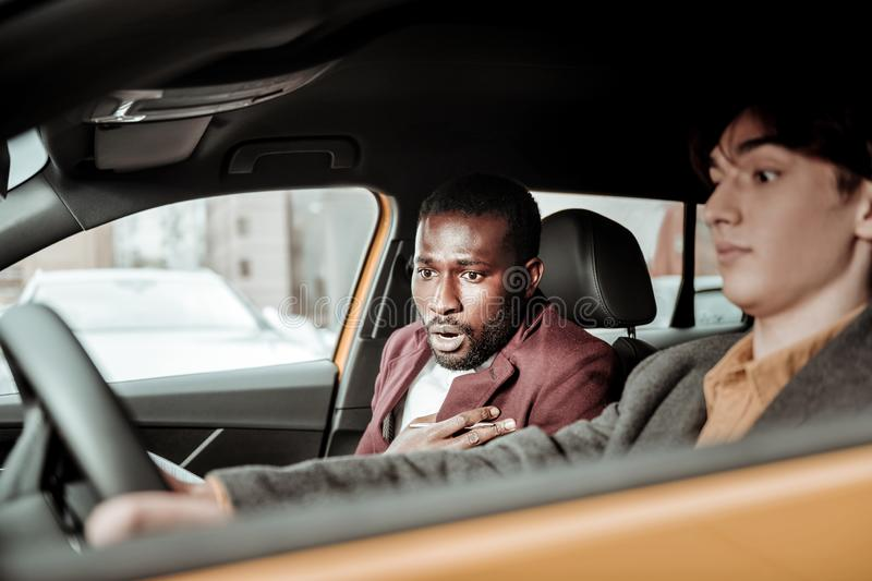 Bearded driving instructor feeling worried while student parking car royalty free stock photos