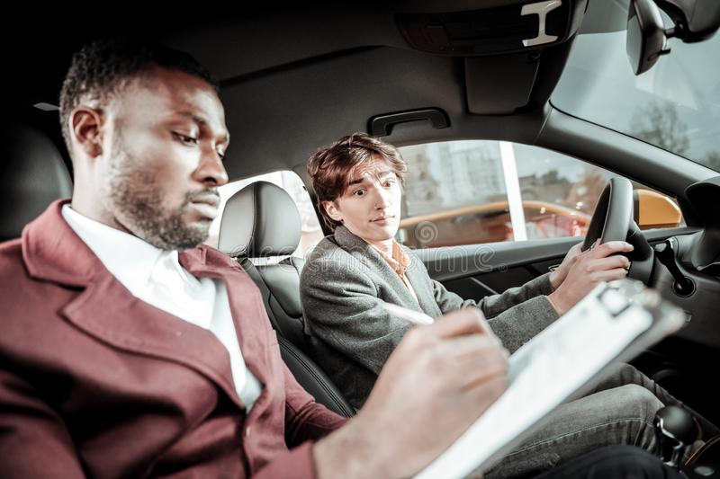 Bearded driving instructor putting marks after test driving. Test driving. Bearded professional driving instructor putting marks after test driving stock images
