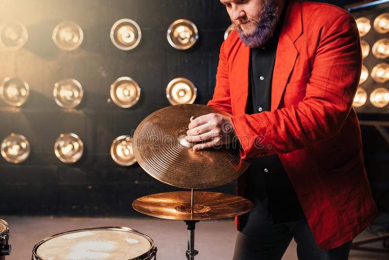 Bearded drummer in red suit on the stage stock photos