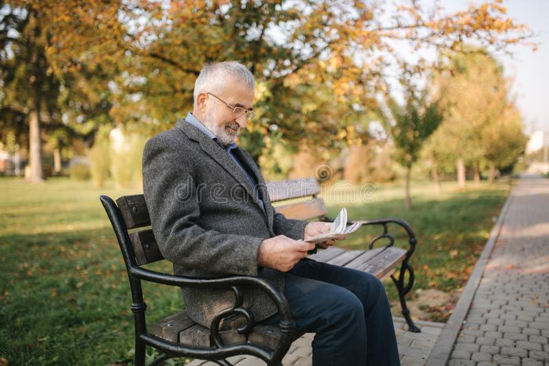 Bearded elderly man in glasses reading newspaper in the autumn park. Handsome gray-haired man sitting on the bench early royalty free stock photos