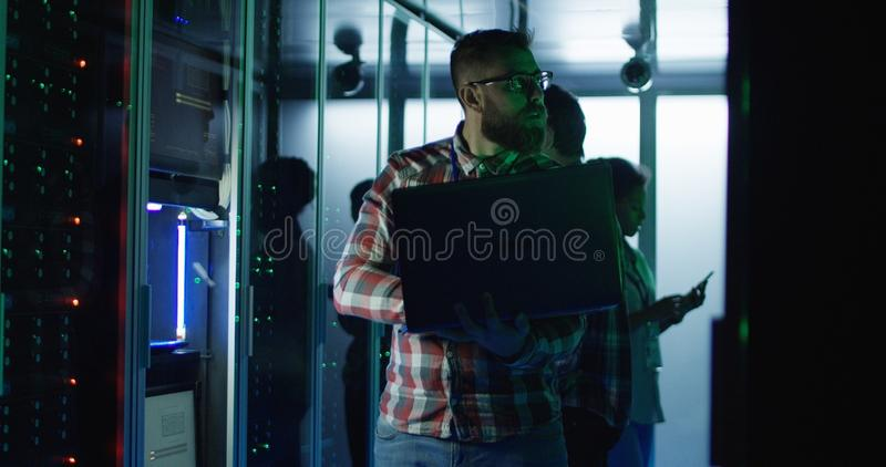 Bearded IT engineer using laptop in server room royalty free stock photography
