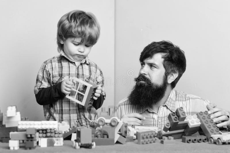 Bearded father and boy play together. Dad and kid build of plastic blocks. Useful toy. Child care development and. Upbringing. Father son game. Father and son stock image
