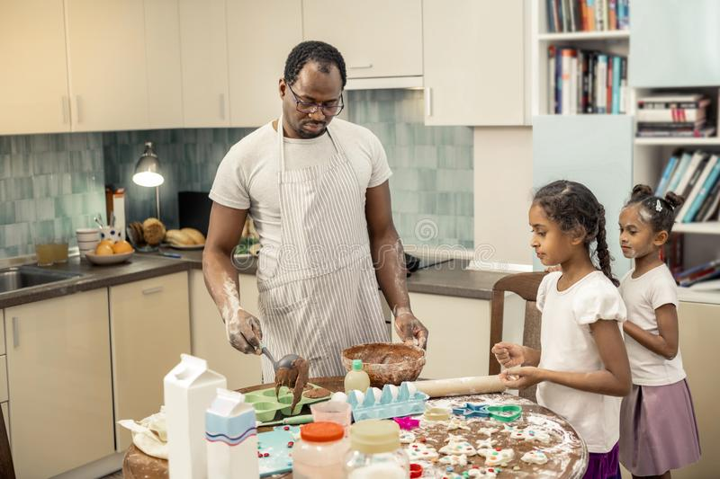 Bearded father cooking chocolate cupcakes with children. Cupcakes with children. Bearded father wearing apron cooking chocolate cupcakes with children stock image