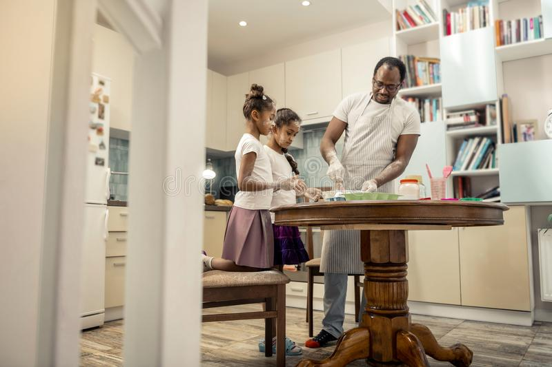 Bearded father feeling amazing while cooking with his girls. Cooking with girls. Bearded dark-haired father feeling amazing while cooking with his girls stock images