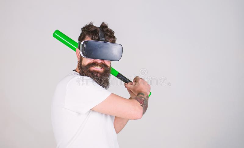 Bearded gamer with agitated look training batting skills, simulation game concept. Man with stylish beard posing with. Baseball bat isolated on gray background stock photography