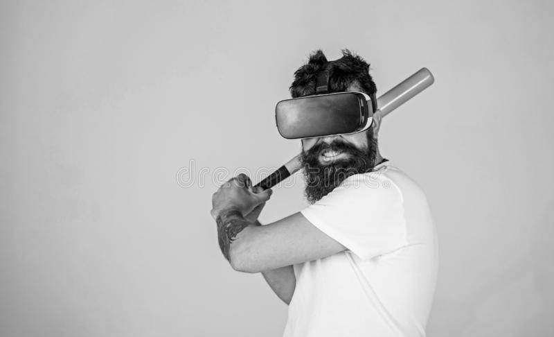Bearded gamer with agitated look training batting skills, simulation game concept. Man with stylish beard posing with. Baseball bat on gray background. Bearded stock photography