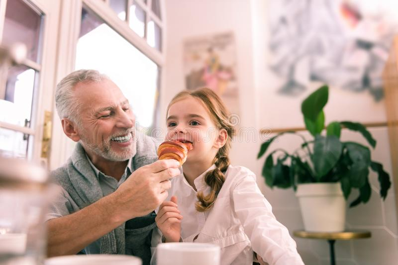 Bearded grandfather feeling cheerful looking at funny granddaughter royalty free stock photo