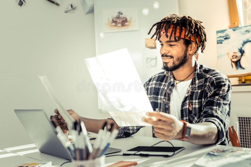 Bearded graphic designer with dreadlocks wearing squared shirt. Squared shirt. Bearded graphic designer with dreadlocks wearing squared shirt and red headband royalty free stock images