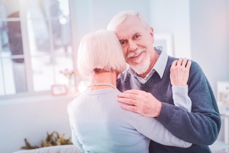 Bearded grey-haired elderly husband hugging his appealing wife stock photo