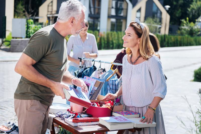 Bearded grey-haired man communicating with beautiful woman at yard sale. Communicating with woman. Bearded grey-haired men communicating with beautiful women at stock photography