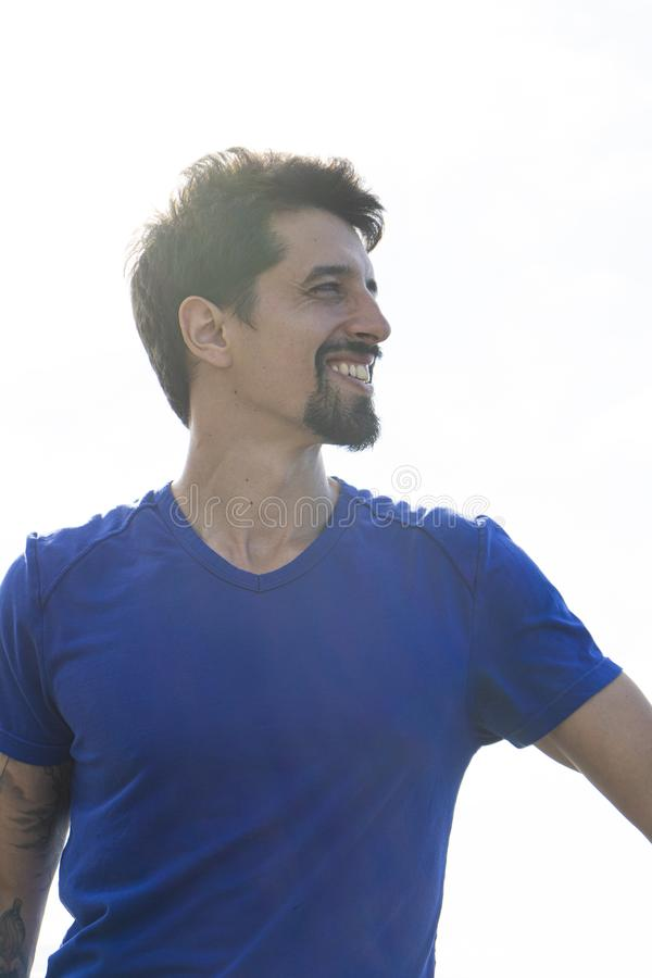 Bearded guy with blue shirt and tattoo arm stand looking to the side with athletic attitude. Smiley man confident with vitality stock photography