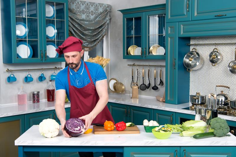 Bearded guy Cook in apron and cap. Chef cutting red cabbage for dinner. Bearded aged Cook in apron and cap. Chef cutting red cabbage for salad on cutting board stock images