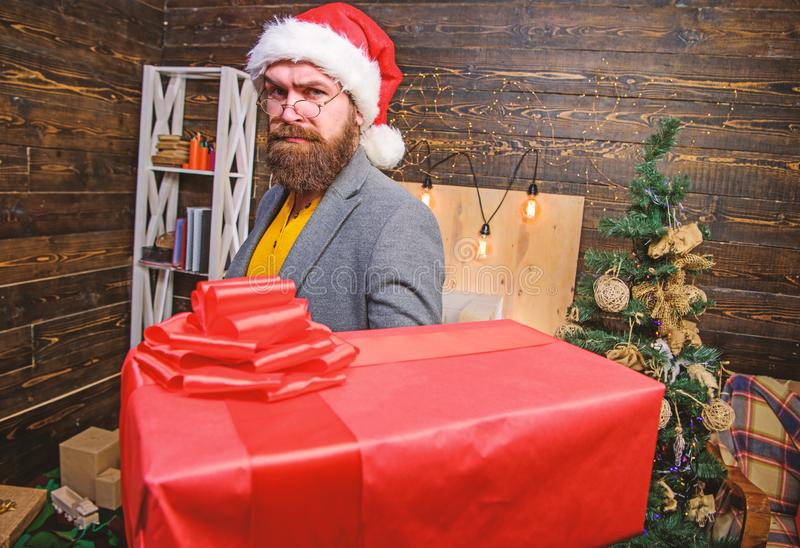 Bearded guy with eyeglasses carry present box. Delivery christmas present. Delivery service. Christmas is coming. Santa. Courier. Gifts delivery. Man santa hat stock images