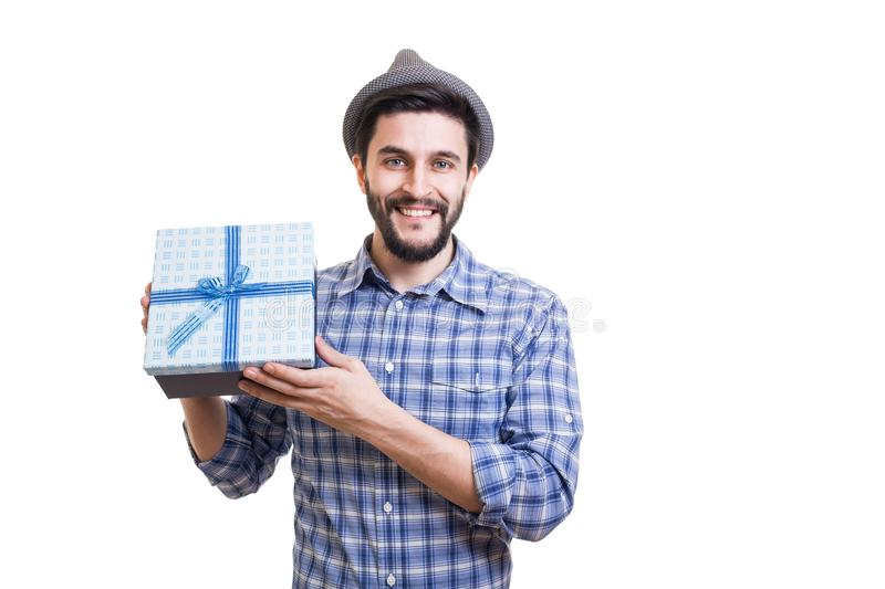 Bearded guy with gift. Young handsome bearded hipster holding gift box in hands royalty free stock photography