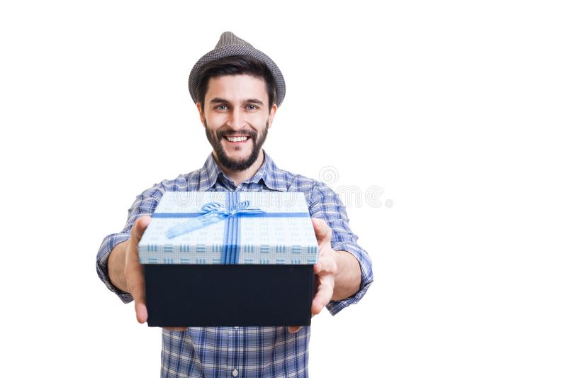 Bearded guy with gift. Young handsome bearded hipster holding gift box in hands stock image