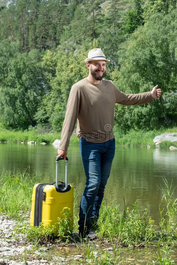 Bearded guy in a hat smiles. A traveler with a yellow suitcase on the shore of a mountain river is waiting for a taxi. A curious stock photo