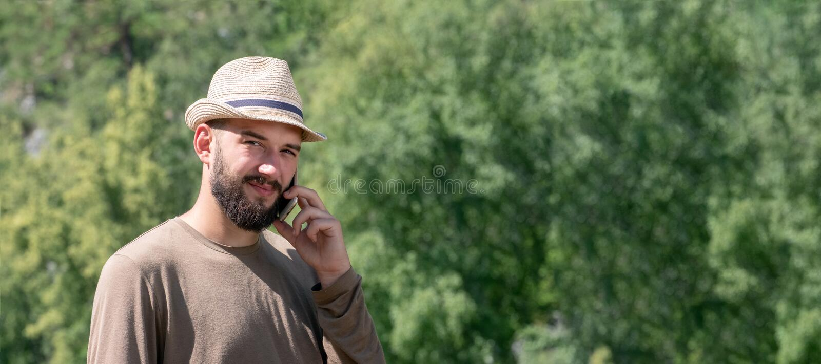 A bearded guy in a hat speaks on the phone and looks sadly into the frame. The lack of telephone communications in nature. The stock photography